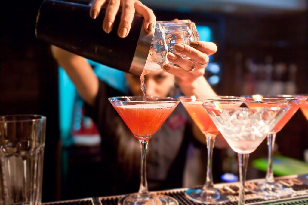 female bartender pouring pink martini drinks