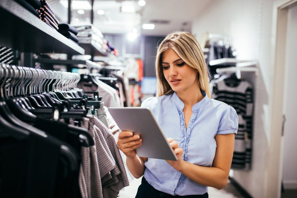store associate with tablet in fashion retail store