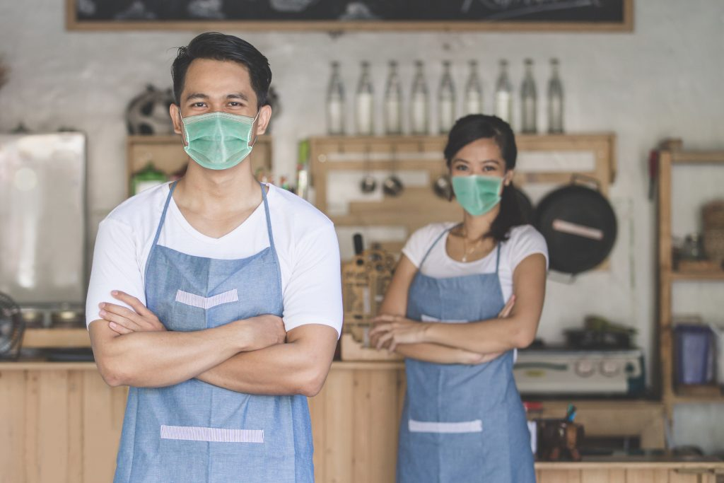 restaurant owners or managers in masks determining restaurant strategies during COVID-19
