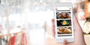 restaurant customer holding phone to purchase meal via restaurant online ordering system