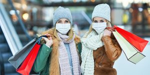 Portrait of two friends shopping together wearing a mask, coronavirus concept