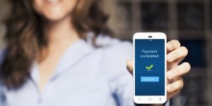 woman holding phone showing that she's just made a mobile payment